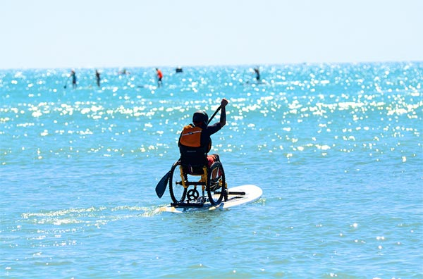 man stand up paddling on wheelchair