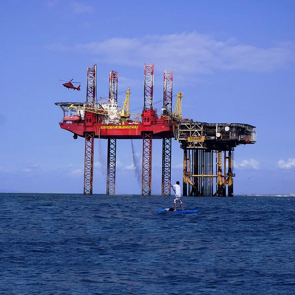 standup paddling next to oil rig