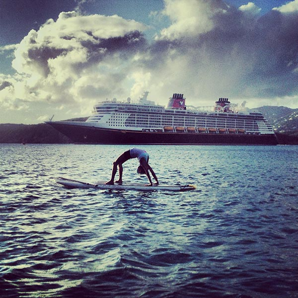 sup yoga in front of cruise ship