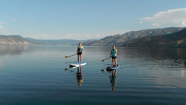 Eileen Meehan Two happy Naramatians (people living in Naramata) Erin Craig & Sue Gunning paddling on beautiful Okanagan Lake, British Columbia.
