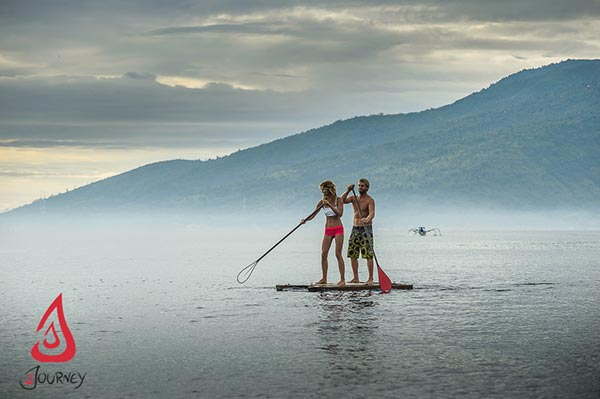 My sister and I doing back bends on a Body Glove paddle board.Journey to North Bali where nature and wilderness abound as you paddle with your lover for a healthy activity filled with fun and adventure.