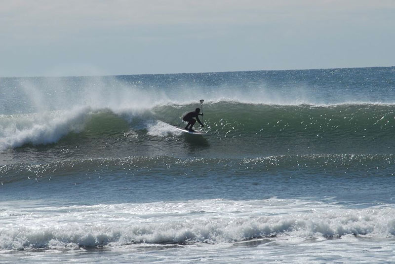 Travis Hayes: Taken at my local beach break in Scarborough Maine in April 2014, by my friend Micky Lawler. Driving down the line on a nice one. I'm field testing a new glove designed by Furnace, a local company specializing in equipment for cold water sports enthusiasts.