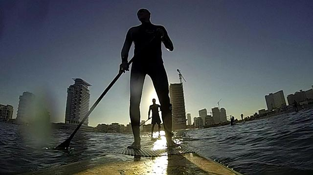 """Yossi Mor: My picture was taken with gopro camera...at the Dolfinarium bean in Tel aviv, Israel The picture reflects composition of urbanic view with 2 sup surfers (me and my friend) at early morning, so the sun was behind us... And we become """"shadow surfers"""" I hope you like it :)"""