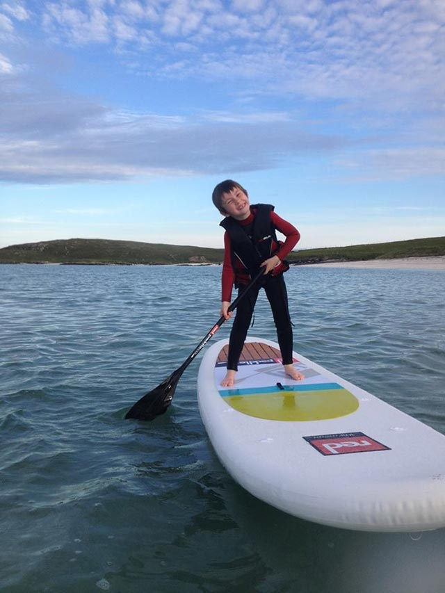 Ed Lowe: Seumas age 6 smiling on his first solo SUP in the cold north western Atlantic waters off Eoligarry, Isle of Barra, Scotland.