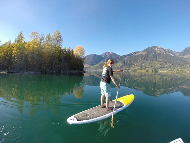 Michael McDonough: Sue Scott psyching herself up to sup 100's of km along the wilderness shores of glassy Kinbasket Lake, near Golden, British Columbia. Don't let the glassy waters fool you!