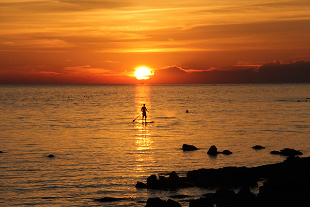 "Primoz Rychly: ""From the sun"". This is the photo of me (Primoz Rychly) suping on the adriatic sea in Croatia. Photo was made by my wife made during the summer. It was a sunny day and a beautiful sunset made it perfect to grab my handmade hollow wooden SUP and go to be ""one with the nature""."