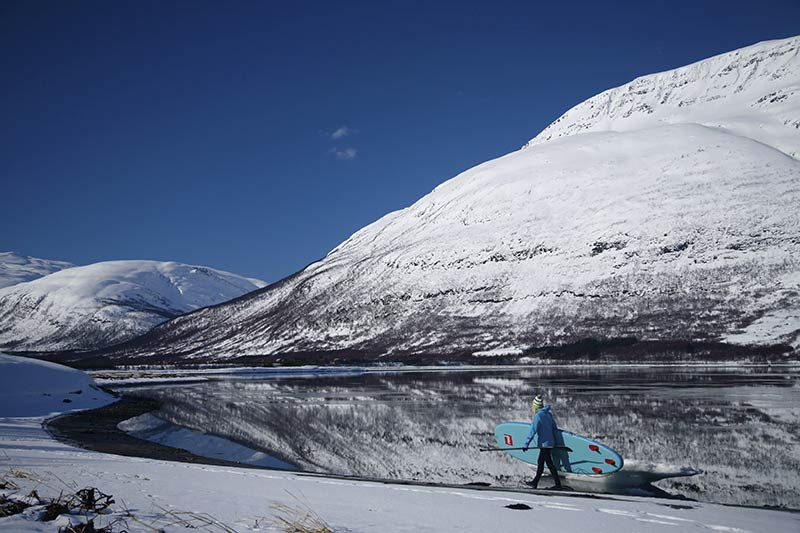 Sanna Juutilainen: Perfect outdoor day in Northern Norway in March 2015 - morning stand up paddling in fjord and afternoon freeskiing in mountains. In the picture Sanna Juutilainen heading to the mirrow stable water in Storfjord. Picture Taneli Brander