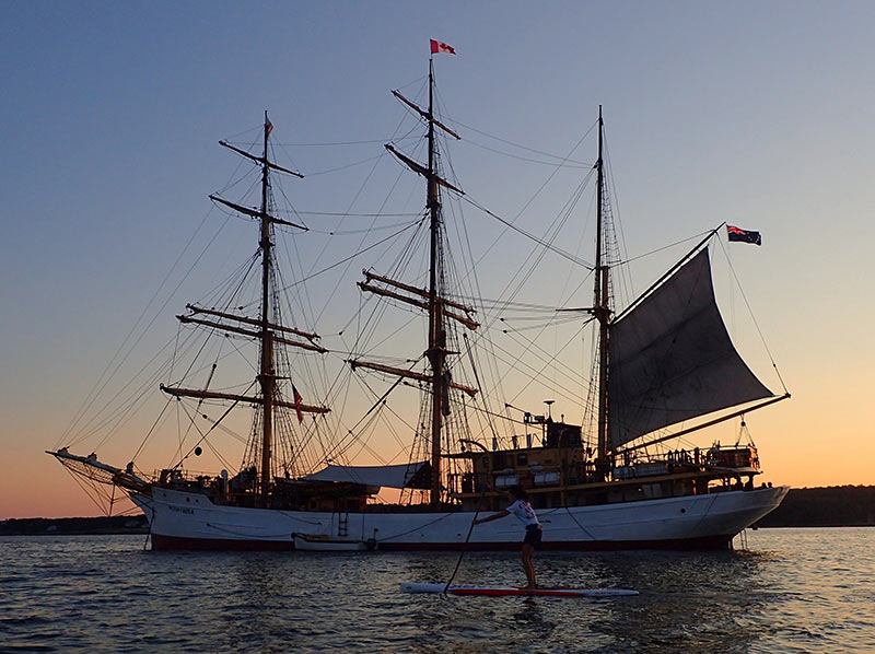 Bill Zinser: Gloucester Massachusetts native Kristina Kalinowsky cruzin past the tall ship Picton Castle at the end of a race training session on Gloucester Harbor.