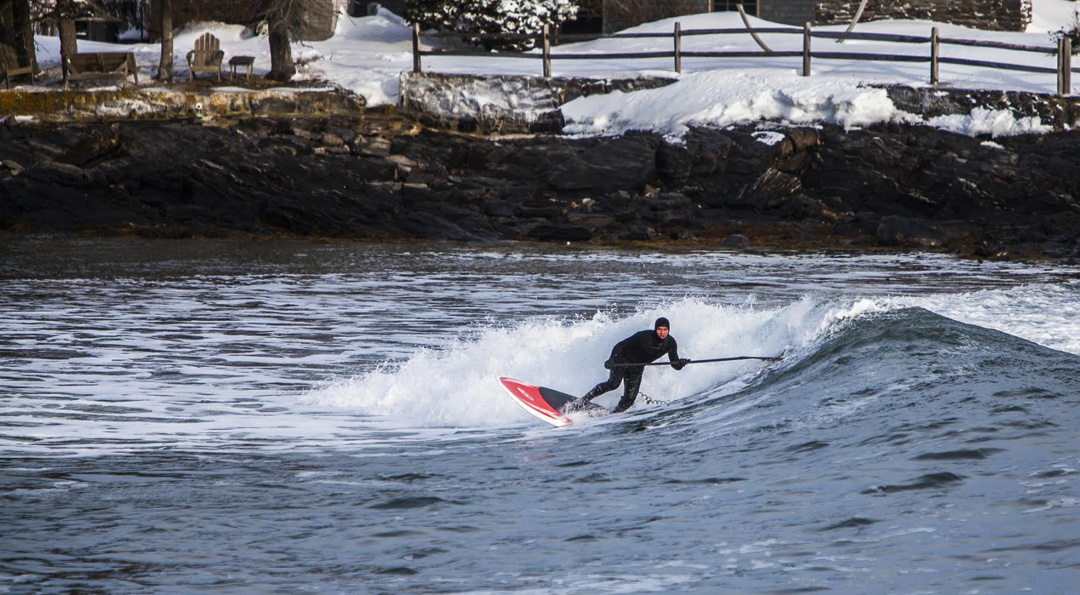 Travis Hayes winter sup surf in New England, Gloucester Massachusetts