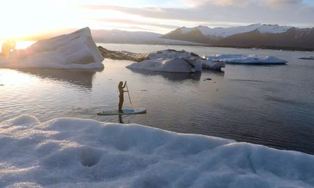 stand up paddler paddling through icebergs in iceland